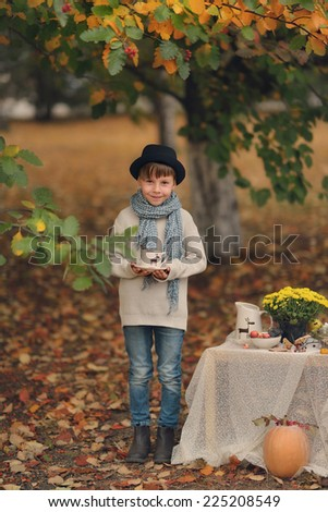 in the autumn forest boy in a hat with a cup at the table - stock photo
