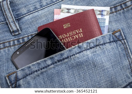 in the back pocket of jeans lie passport, mobile phone and money