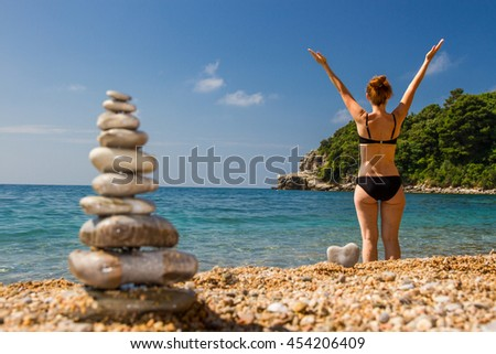 In the background there is a girl back to us,the girl in focus, the girl raised her hands up,in the foreground is the pyramid of pebbles/The girl and the pyramid of pebbles/Spa treatments on fresh air - stock photo