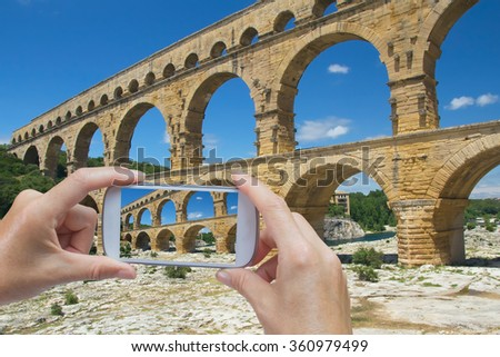 In the bottom left of the photo are hands holding smart phone, whose screen contains photo of Pont du Gard. Background of the photo contains also Pont du Gard.(France)