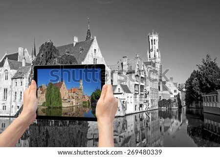 In the bottom left of the photo are hands holding tablet, whose screen contains color photo of the Rozenhoedkaail. Background of the photo contains monochromatic photo of Bruges (Bruges, Belgium) - stock photo