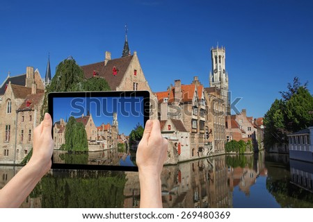 In the bottom left of the photo are hands holding tablet, whose screen contains color photo of the Rozenhoedkaail. Background of the photo contains the same color photo of Bruges (Bruges, Belgium) - stock photo