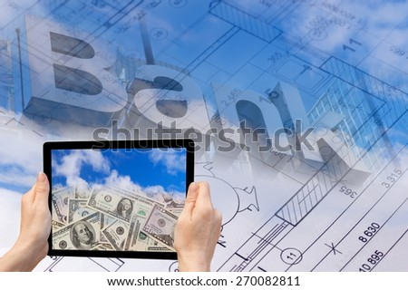 In the bottom left of the photo are hands holding tablet, whose screen contains photo of US dollar banknotes falling from the sky.  Background contains abstract of the blueprint and bank inscription - stock photo