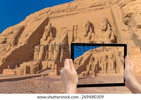In the bottom right of the photo are hands holding tablet, whose screen contains photo of the Abu Simbel TempleI.  Background of the photo contains also Abu Simbel Temple of King Ramses II. ( Egypt)  - stock photo