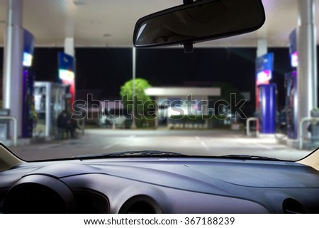 In the car, blur image of gas station as background.