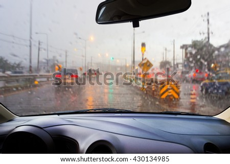 In the car, blur image of heavy rain on the road at night as background.