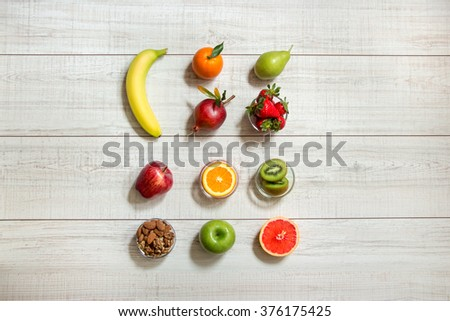 In the center 3 columns of different ripe fruits banana, grapefruit, kiwi, pear, apples, orange, strawberries, pomegranate,nuts on light wood background. Different fruits, nuts. Horizontal. Top view. - stock photo