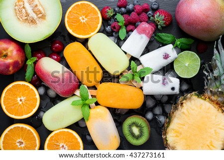 In the center on ice cubes variety of sorbet and ice cream cones near ingredients fruits and berries on black background. Summer coolness of ice cream and sorbet cones. Horizontal. Top view. - stock photo