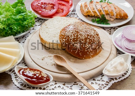 In the center the bun cut in half on a wooden plank around ingredients for a sandwich cheese, lettuce, tomato, chicken, onion, mayonnaise, ketchup on the wooden background. Cooking chicken sandwich.