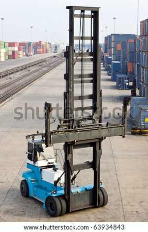 in the container storage area, we can see too much lifting crane and colorful stack under the blue sky - stock photo