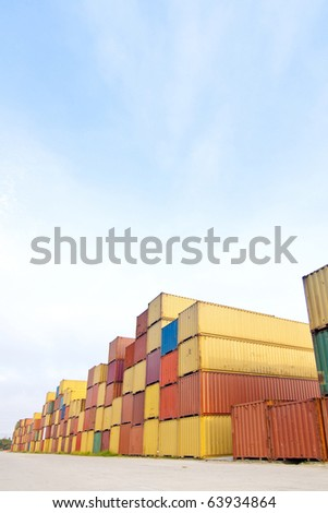 in the container storage area, we can see too much lifting truck and colorful stack under the blue sky - stock photo