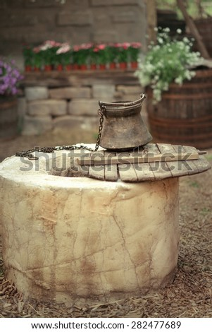 in the courtyard on the background of flowers and barrels round the well with a bucket - stock photo