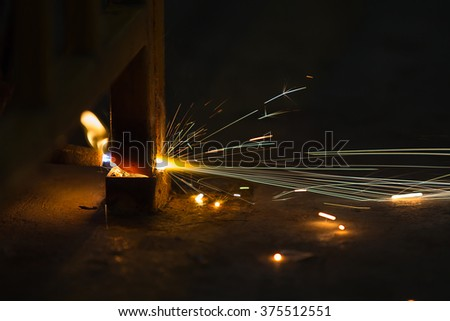 In the dark, gas cutting steel with sparks light blur and bokeh