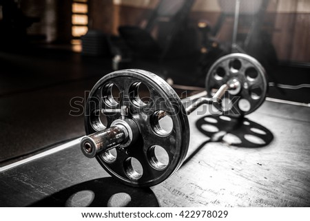 In the dark mood, Light and shadow on a dumbbell in the black background. - stock photo