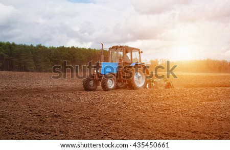 In the early,spring morning,because of the wood the bright sun ascends.The tractor goes and pulls a plow,plowing a field before landing of crops.On the earth dry stalks of a last year's sunflower lie. - stock photo