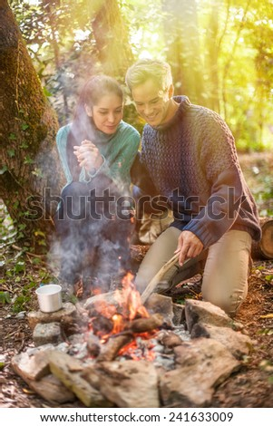in the evening, a couple heats up near a campfire in the woods, their backpack behind them - stock photo
