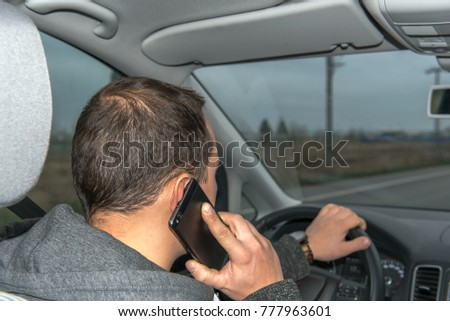 In the evening, a young man drives his car across the streets and uses his cell phone to make a phone call. The driver is distracted by telephoning off the road. Concept: safety and road traffic