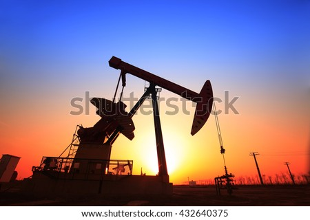 In the evening, the silhouette of the oil pump - stock photo