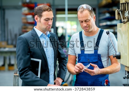 in the factory- young boss and worker in conversation - stock photo