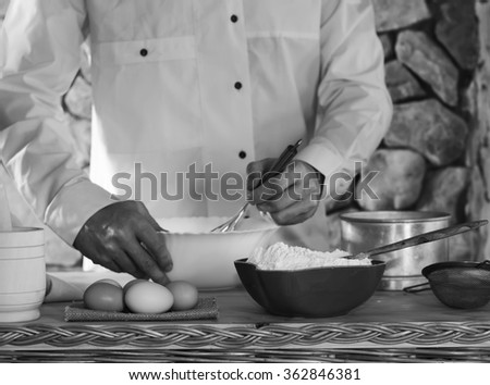 in the foreground a bowl with flour, eggs, sieve and mortar in the background a man dressed in white chef whips whisk the batter. rustic kitchen concept, selective focus. black and white photo - stock photo