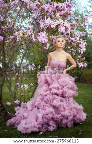 In the garden under the magnolia tree is a girl in a pink dress lush. Dress with jeweled fringe. - stock photo