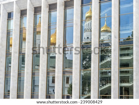 In the glass walls of the palace are reflected walls, drums and the dome of the Assumption Cathedral ./Russia , Moscow, Kremlin , the State Kremlin Palace. - stock photo