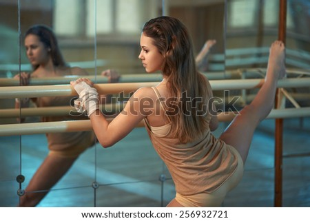 in the hall girl doing stretching near Barre - stock photo