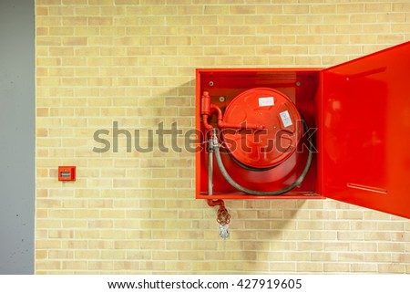 in the hallway of a nice building, there is an fire hose - stock photo