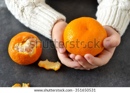 In the hands of the child's Mandarin  - stock photo