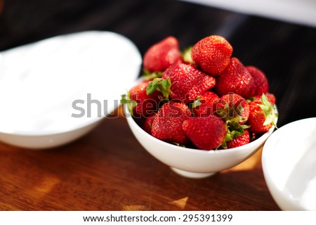 In the kitchen, dear baker chef prepared a large plate of strawberries that have to decorate her wedding cake - stock photo