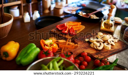 In the kitchen of the restaurant goes all the preparations for dinner, green pepper is on the board, next to sliced mushrooms, cherry tomatoes washed - stock photo