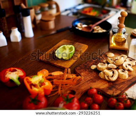 In the kitchen of the restaurant goes all the preparations for dinner, half green pepper lays on a board near pgriby sliced, washed cherry tomatoes - stock photo