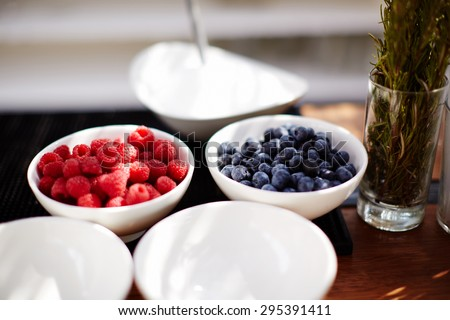 In the kitchen, pastry shops in two white plates are berries fresh raspberries and currants plucked from the bush - stock photo