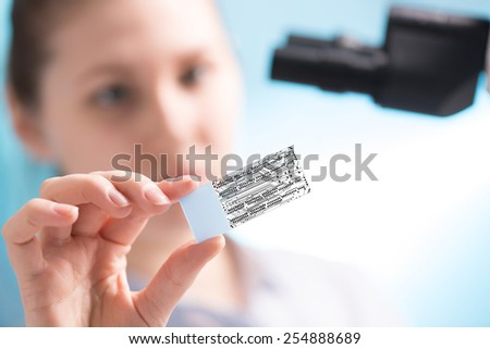 In the laboratory technician looks at slides through a microchip - stock photo