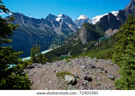 In the Lake Louise area of the Canadian Rockies showing, Lake Louise, Mirror Lake and Lake Agnes with the snow covered summits of Mounts Temple, Lefroy and Victoria in the background. - stock photo
