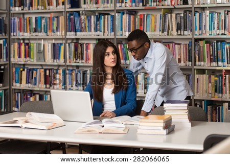 In The Library - Handsome Two College Students With Laptop And Books Working In A High School - University Library - Shallow Depth Of Field