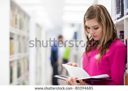 in the library - pretty, female student with laptop and books working in a high school library (color toned image) - stock photo