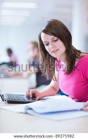 in the library - pretty female student with laptop and books working in a high school library  (color toned image) - stock photo