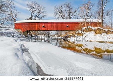 In the midst of a snowy winter landscape, the historic Oakalla Covered Bridge crosses Big Walnut Creek in rural Putnam County, Indiana. - stock photo