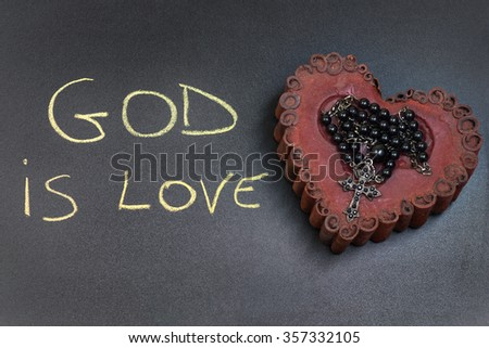 """In the picture a rosary iron placed over a heart of red wax, on the left side the inscription """"God is Love"""" made with a crayon. - stock photo"""