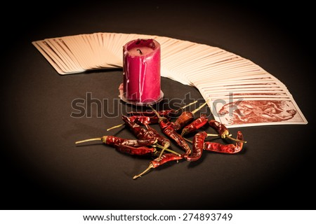 In the pictured a deck of cards open fan , a red candle and red pepper dry. - stock photo