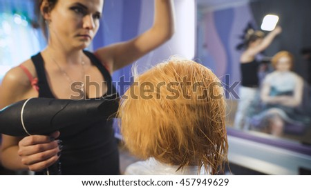 In the professional salon hairstyle on the girl's head dried hairdryer. After staining and washing hair. The girl in a black dress with blond hair