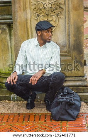 In the rain, a foggy, wet feel. Wearing a long sleeve shirt, a ivy cap,  carrying a traveling bag,  a young black man is squatting against a wall, looking around, waiting for you. A young traveler.