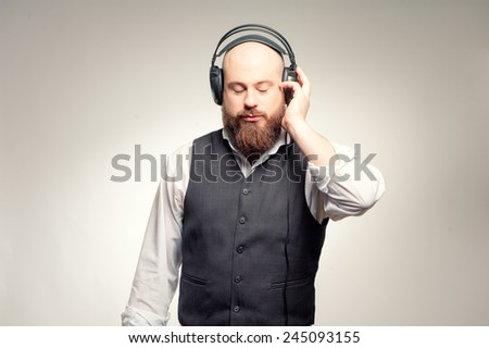 In the rhythm of my music. Confident young bearded man in headphones standing against grey background and listening to the music - stock photo
