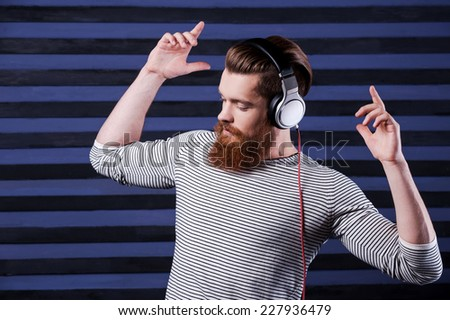In the rhythm of my music. Confident young bearded man in headphones standing against stripped background and listening to the music - stock photo