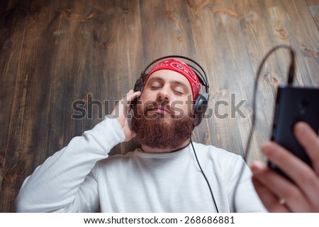 In the rhythm of my music. Relaxed young bearded man in headphones with smartphone leaning on wooden wall and listening to the music. - stock photo