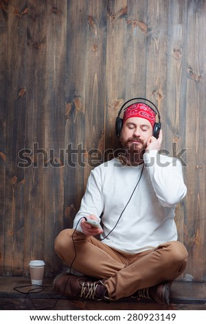 In the rhythm of my music. Relaxed young bearded man in headphones with smartphone sitting near wooden wall and listening to the music. - stock photo