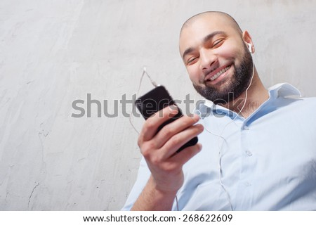 In the rhythm of my music. Smiling young bearded man in headphones with smartphone leaning on the grey wall and listening to the music. - stock photo