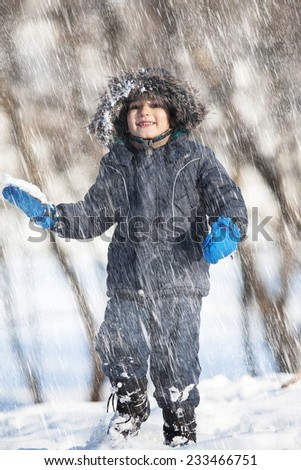 In the snowfall. Cute boy walk in the winter park in sunny day - stock photo