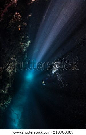 In the Solomon Islands, a free diver descends into a reef crevice illuminated by brilliant beams of sunlight. - stock photo